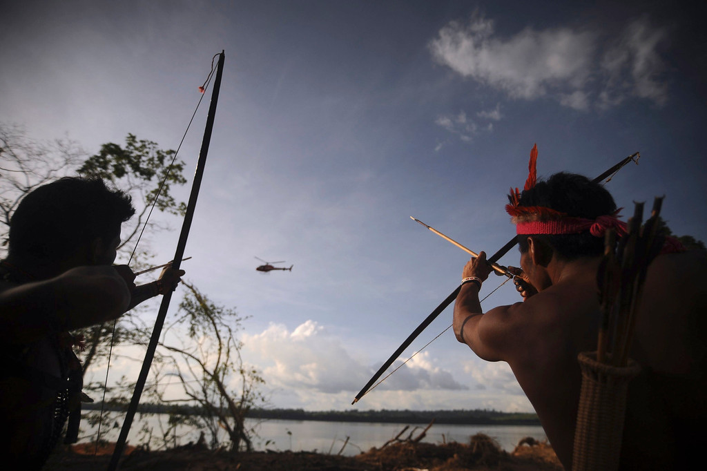 . Indigenous people point their bows and arrows at a police helicopter flying over the occupied barrier of the Belo Monte Dam\'s construction site in Vitoria do Xingu, near Altamira in northern Brazil June 15, 2012. The area was occupied by around 300 activists, indigenous people, fishermen and coastal community members affected by the project as they protested against the construction of the Belo Monte Hydroelectric power plant, according to the activists. REUTERS/Lunae Parracho