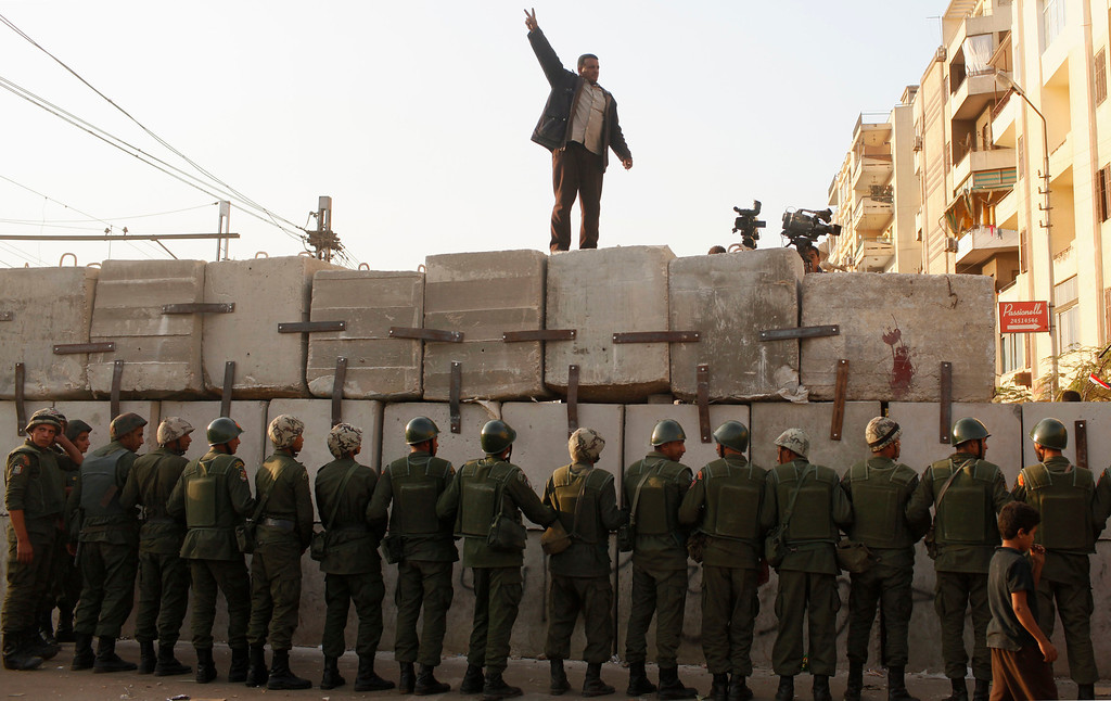 . An anti-Mursi protester chants slogans on a newly built barrier in front of soldiers guarding outside the Egyptian presidential palace in Cairo December 9, 2012.  REUTERS/Asmaa Waguih
