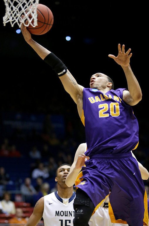 . Albany forward Gary Johnson drives against Mount St. Mary\'s in the first half of a first-round game of the NCAA college basketball tournament, Tuesday, March 18, 2014, in Dayton, Ohio. (AP Photo/Al Behrman)