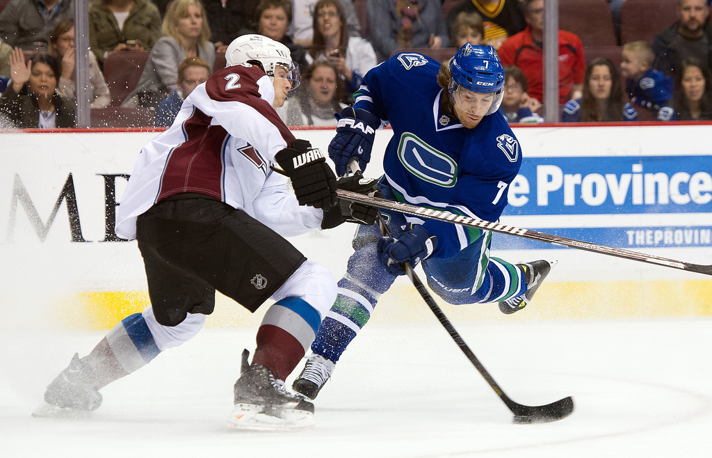 . David Booth #7 of the Vancouver Canucks fires a shot on net through the check of Nick Holden #2 of the Colorado Avalanche during the second period in NHL action on April 10, 2014 at Rogers Arena in Vancouver, British Columbia, Canada.  (Photo by Rich Lam/Getty Images)