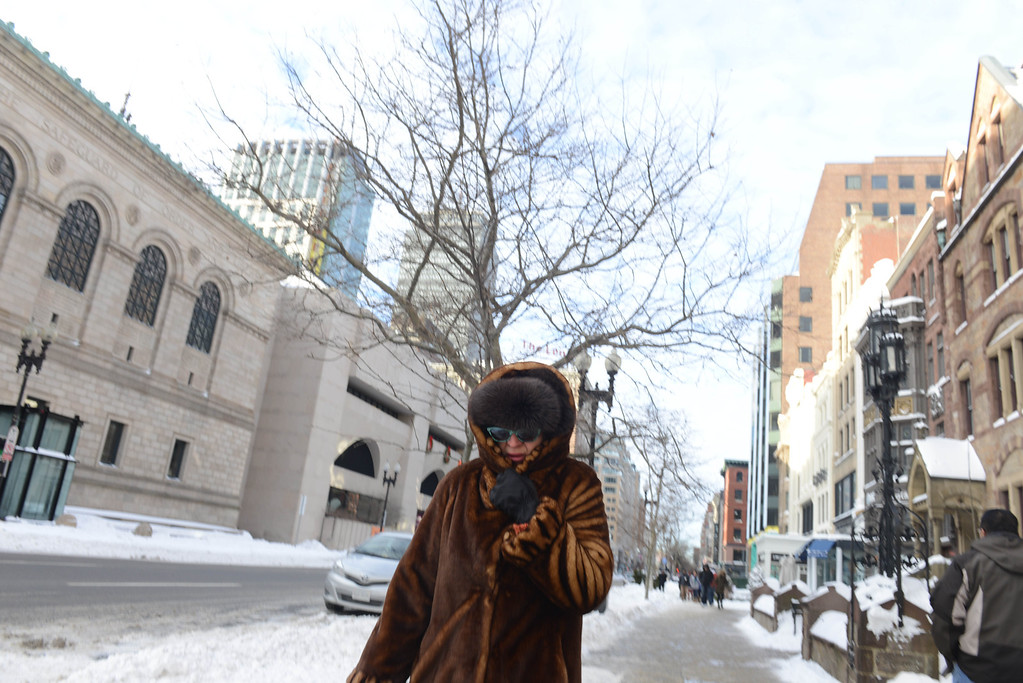 . A woman walks down Boylston Street a day after a winter storm January 4, 2014 in Boston, Massachusetts. The storm began mid-day Thursday with heavy snows overnight into Friday bringing with it temperatures in the low single digits and a minus degree wind chill factor.  (Photo by Darren McCollester/Getty Images)