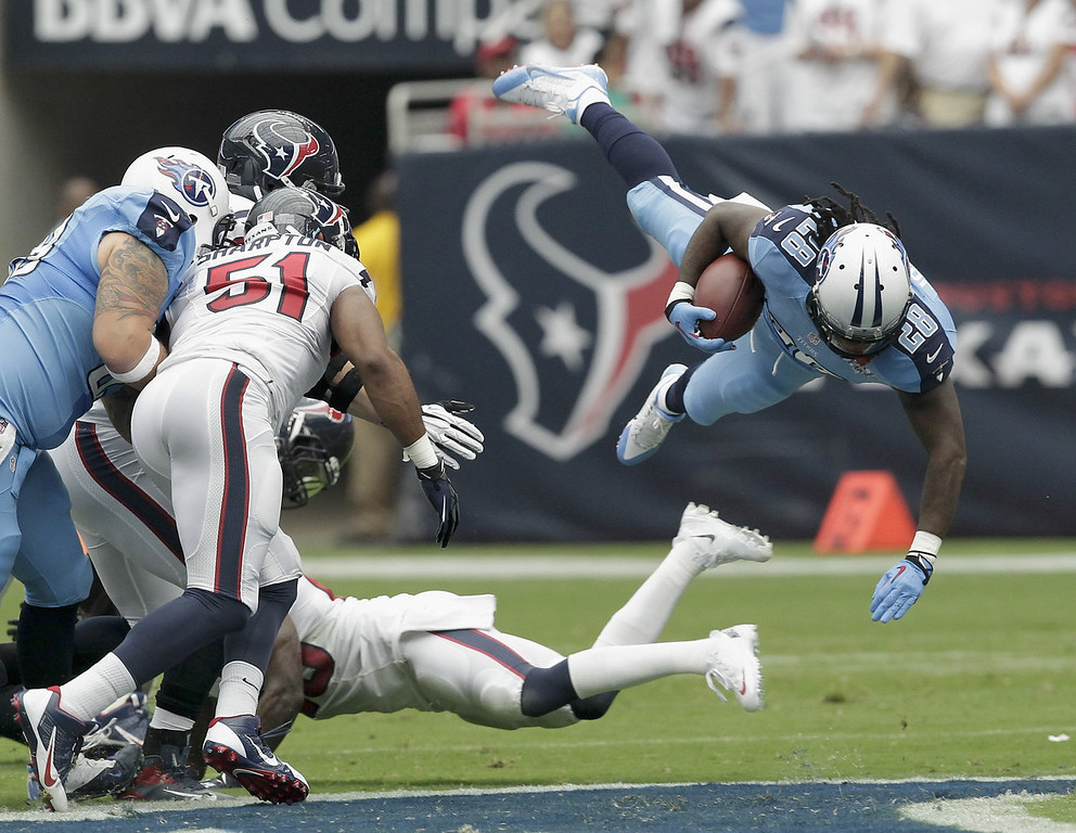 . Chris Johnson #28 of the Tennessee Titans is tripped up as he rushes in the first quarter against the Houston Texans at Reliant Stadium on September 15, 2013 in Houston, Texas.  (Photo by Bob Levey/Getty Images)