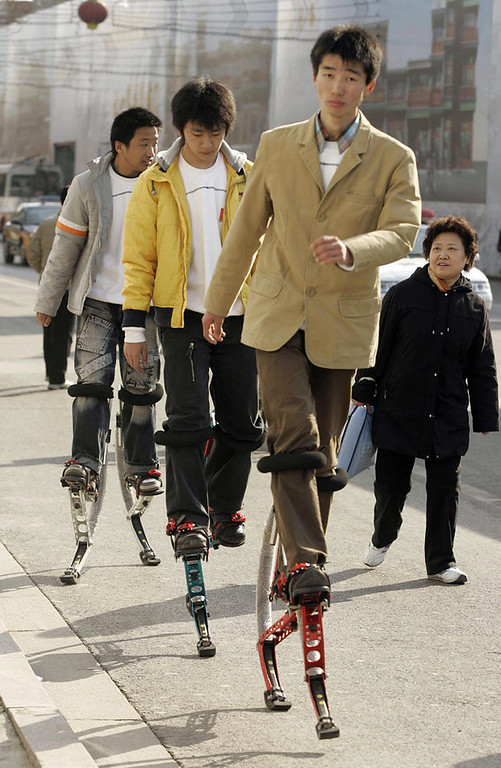 . A woman watches as three men hop by on sprung contraptions attached to their legs on a street in Beijing, 06 March 2007.  Chinese Premier Wen Jiabao opened the annual session of China\'s parliament thise week with a call for more sustainable economic growth, warning development was exacting too great a social and environmental toll. AFP PHOTO/Peter PARKS