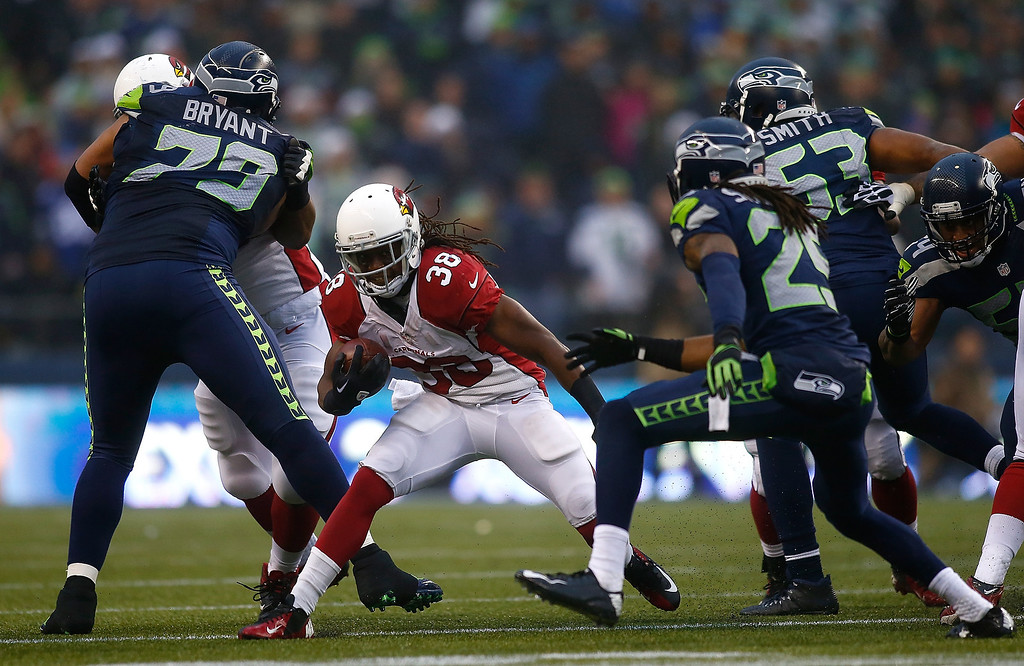. Andre Ellington #38 of the Arizona Cardinals runs the ball against Richard Sherman #25 of the Seattle Seahawks on December 22, 2013 at CenturyLink Field in Seattle, Washington.  (Photo by Jonathan Ferrey/Getty Images)