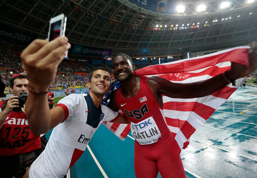 . USA\'s Justin Gatlin, right, poses for a photograph after winning silver in the Men\'s 100-meter final at the World Athletics Championships in the Luzhniki stadium in Moscow, Russia, Sunday, Aug. 11, 2013. (AP Photo/Ivan Sekretarev)
