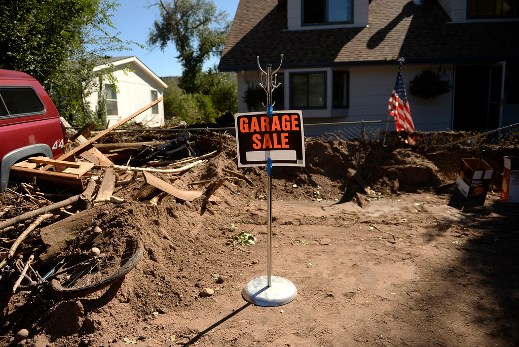 . A Lyons resident put up a garage sale sign as a joke in front of their flood damaged home in Lyons, September 20, 2013. Residents start to clean up after a massive flood hit the area. (Photo By RJ Sangosti/The Denver Post)