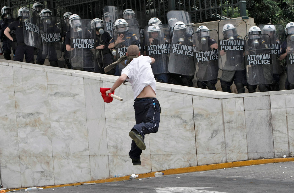 . A demonstrator hurls projectiles at riot police near the Greek parliament in Athens during a nationwide strike in Greece, May 5, 2010.  Greece braced for a day of demonstrations during a nationwide strike by civil servants protesting the announcement of draconian austerity measures.       REUTERS/John Kolesidis