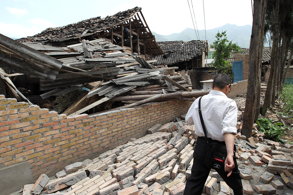 . YA\'AN, CHINA - APRIL 20:  A man walks across rubble caused by an earthquake which hit China\'s Sichuan Province on April 20, 2013 in Ya\'an, Sichuan Province of China. The devastating earthquake hit the region in the morning claiming over 100 lives and injuring thousands.  (Photo by ChinaFotoPress/Getty Images)