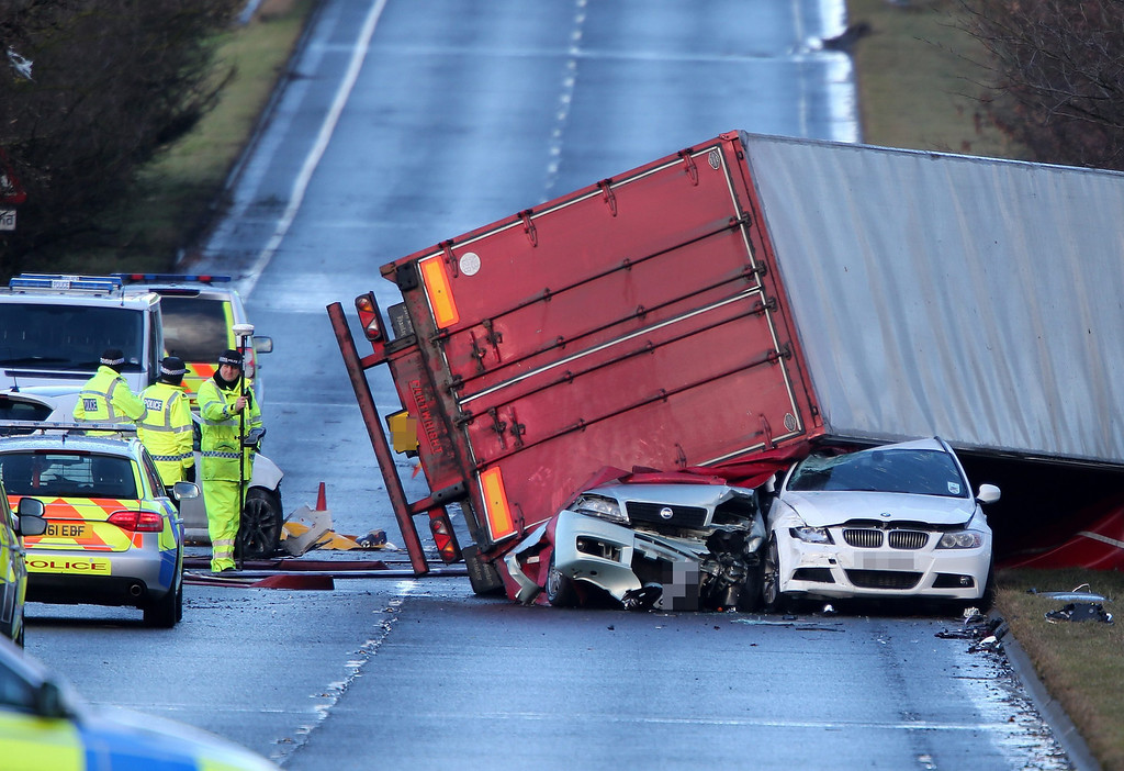 . Police at the scene where a lorry driver has died after his heavy good vehicle toppled on to a number of cars on the A801 in West Lothian, Scotland, 05 December 2013.  A powerful Atlantic winter storm made landfall on 05 December 2013 in Scotland, knocking out the region\'s transport, as the rest of Northern Europe braced for hurricane-force winds.  EPA/ANDREW MILLIGAN  EDITORS NOTE NUMBER PLATE PIXELATED BY PICTURE DESK
