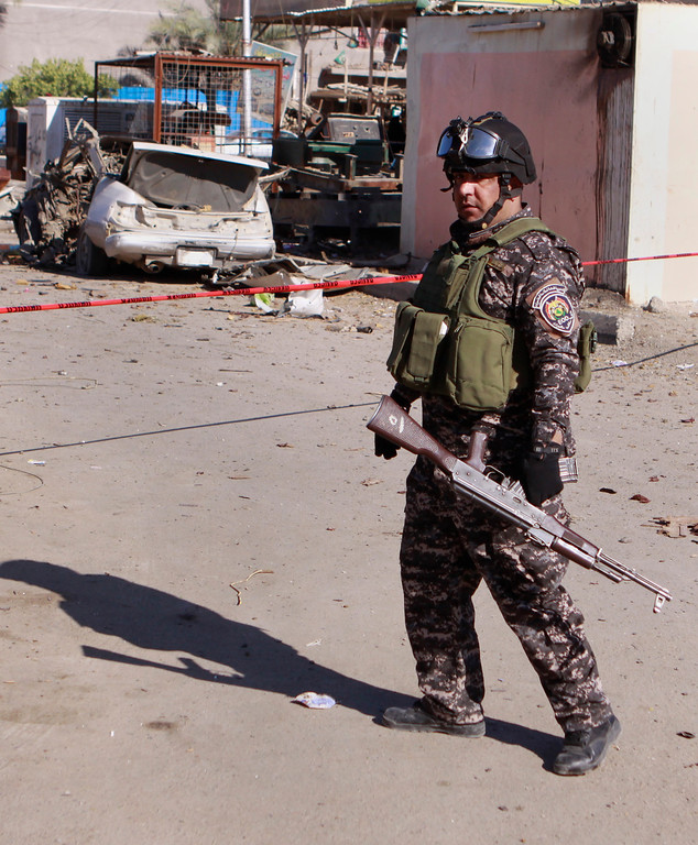 . A police man stands guard at the scene of a car bomb attack in the Shiite stronghold of Sadr City, Baghdad, Iraq, Tuesday, March 19, 2013.  (AP Photo/ Karim Kadim)