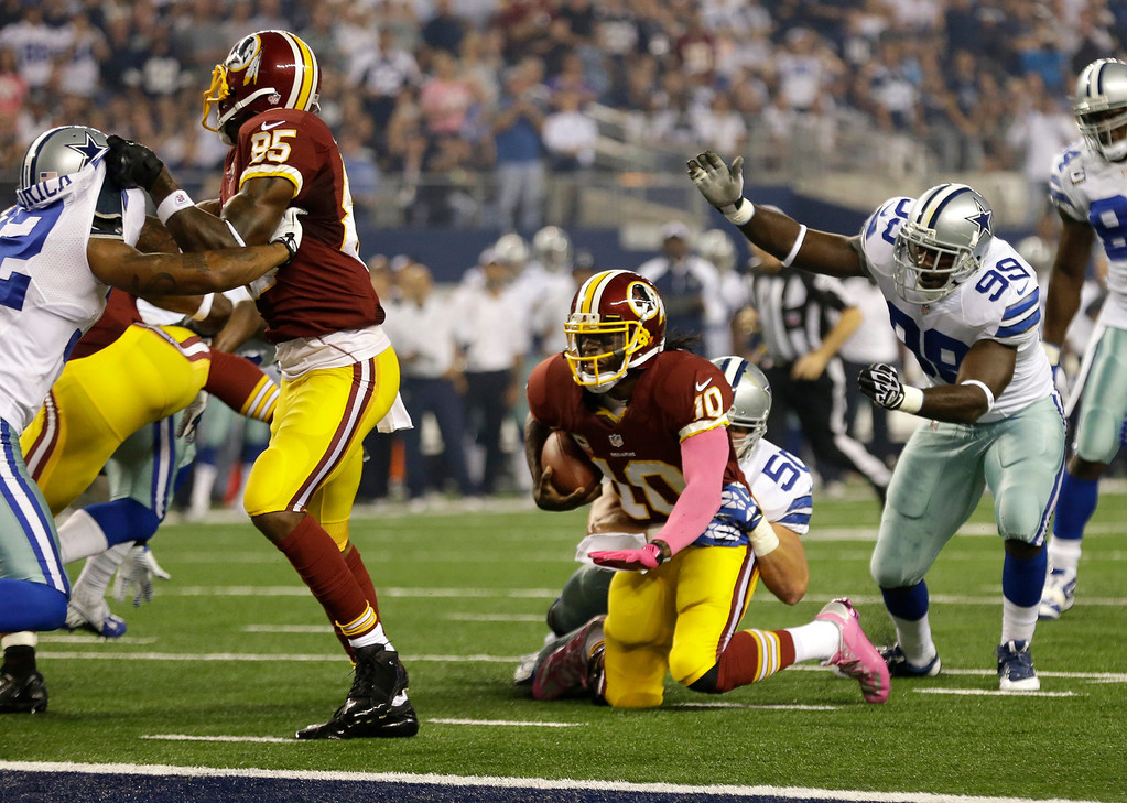 . Washington Redskins wide receiver Leonard Hankerson (85) helps against the pressure as quarterback Robert Griffin III (10) is stopped shy of the end zone by Dallas Cowboys middle linebacker Sean Lee (50) in the first half of an NFL football game, Sunday, Oct. 13, 2013, in Arlington, Texas. The Cowboys defensive end George Selvie (99) watches on the play.  (AP Photo/LM Otero)