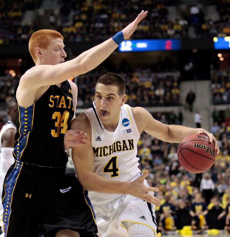 . Michigan Wolverines Mitch McGary (R) drives on South Dakota State Jackrabbits Tony Fiegen during the first half of their second round NCAA tournament basketball game in Auburn Hills, Michigan March 21, 2013.  REUTERS/Jeff Kowalsky
