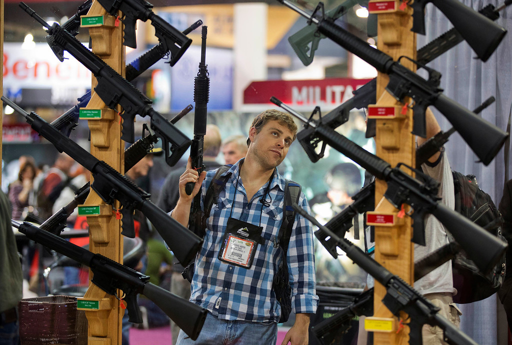 . Michael Kiefer, of DeFuniak Springs, Fla., checks out a display of rifles at the Rock River Arms booth during the 35th annual SHOT Show, Thursday, Jan. 17, 2013, in Las Vegas.  (AP Photo/Julie Jacobson)