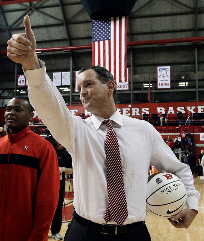 . Rutgers coach Mike Rice waves as he holds a ball presented to him for his 100th career win after Rutgers defeated Cincinnati in an NCAA college basketball game in Piscataway, N.J on Jan. 28, 2012. ESPN\'s airing on Tuesday, April 2, 2013, of a videotape of Rutgers basketball coach Mike Rice using gay slurs, shoving and grabbing his players and throwing balls at them in practice over the past three seasons has the university\'s athletic director reconsidering his decision not to fire the coach. Scarlet Knights AD Tim Pernetti was given a copy of the video in late November by a disgruntled former employee, and he suspended Rice for three games, fined him $50,000 and made him undergo anger management classes for inappropriate behavior after investigating it. (AP Photo/Mel Evans,file)