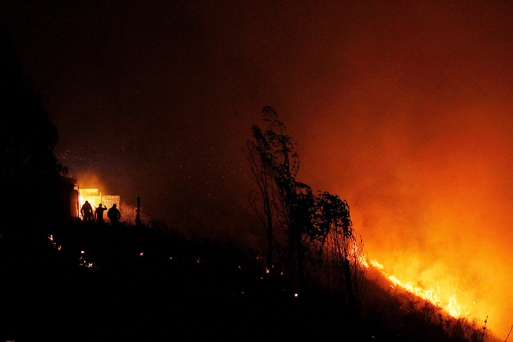 . People prepare to leave as a forest fire rages towards urban areas in the city of Valparaiso, Chile, Sunday April 13, 2014. Authorities say the fires have destroyed hundreds of homes, forced the evacuation of thousands and claimed the lives of at least seven people.  ( AP Photo/ Luis Hidalgo)