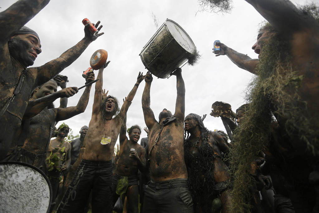 ". Mud covered revelers dance and sing at the ""Bloco da Lama\"" or \""mud street partyî underneath an overcast sky in Paraty, Brazil, Saturday, March 1, 2014. The \""Bloco da Lama\"" was founded in 1986 by two local teens who became local Carnival sensations after they appeared in the city\'s historic downtown covered in mud following a crab hunting expedition in a nearby mangrove forest, said Diana Rodrigues, who was hired by Paraty\'s City Hall to explain the history of the ìblocoî to foreigners. (AP Photo/Nelson Antoine)"
