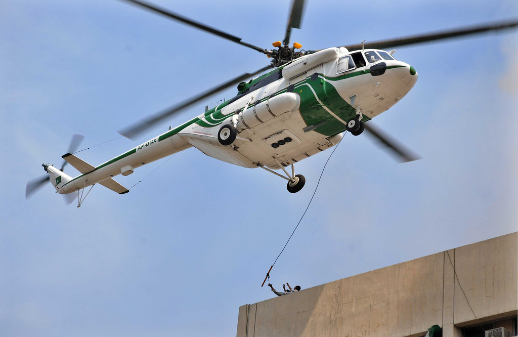 . A Pakistani army helicopter rescues people from a burning building in Lahore on May 9, 2013.  AFP PHOTO/ Arif ALIArif Ali/AFP/Getty Images