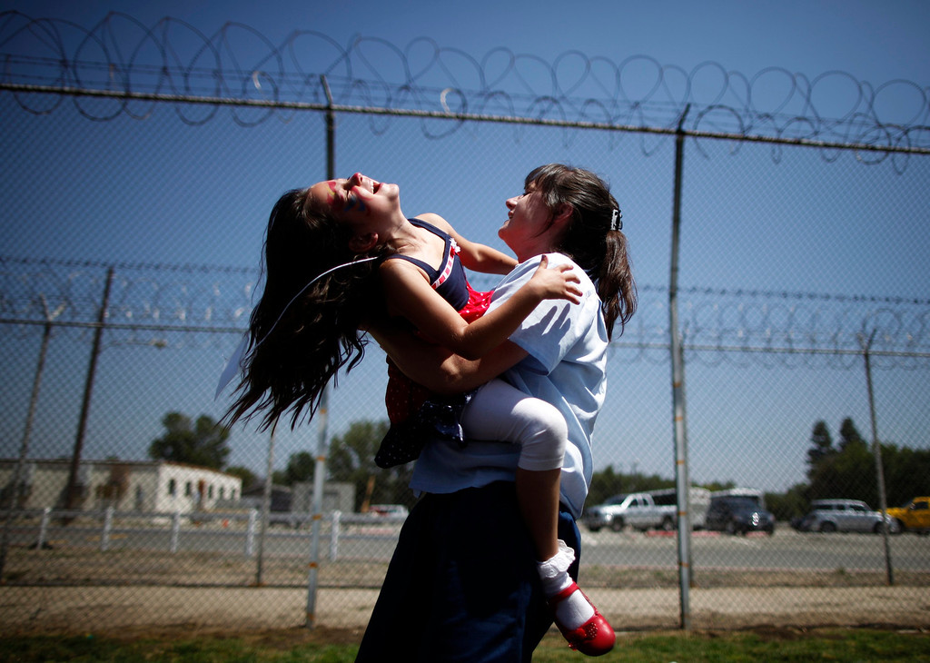 . Cori Walters, 32, (R) hugs her daughter Hannah Walters, 6, at California Institute for Women state prison in Chino, California May 5, 2012. An annual Mother\'s Day event, Get On The Bus, brings children in California to visit their mothers in prison. Sixty percent of parents in state prison report being held over 100 miles (161 km) from their children.    REUTERS/Lucy Nicholson