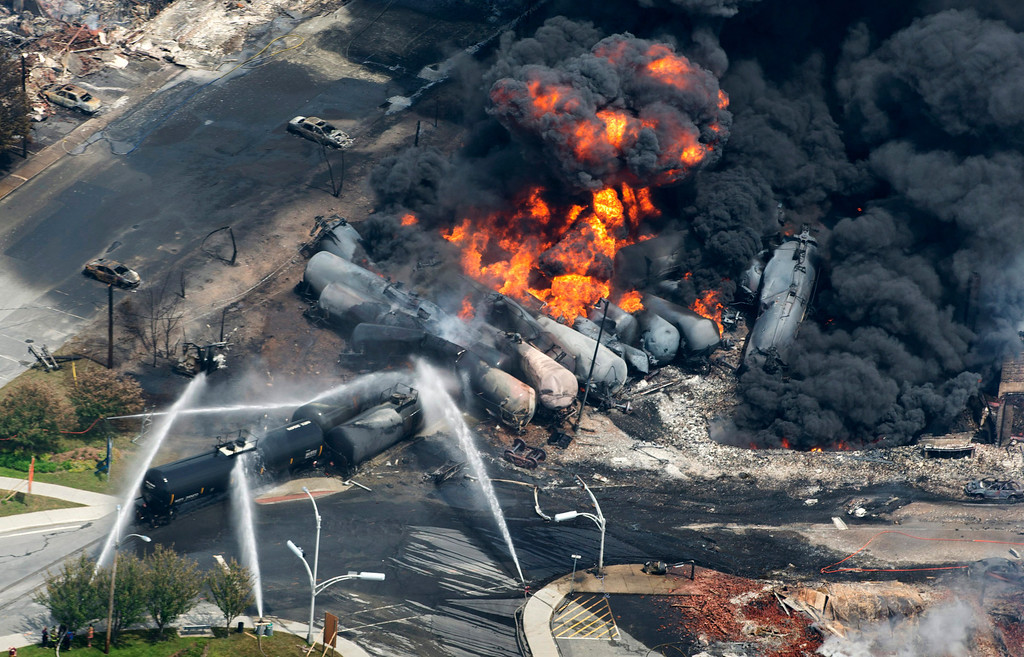 . Smoke rises from railway cars that were carrying crude oil after derailing in downtown Lac Megantic, Quebec, Canada, Saturday, July 6, 2013. A large swath of Lac Megantic was destroyed Saturday after a train carrying crude oil derailed, sparking several explosions and forcing the evacuation of up to 1,000 people. (AP Photo/The Canadian Press, Paul Chiasson)