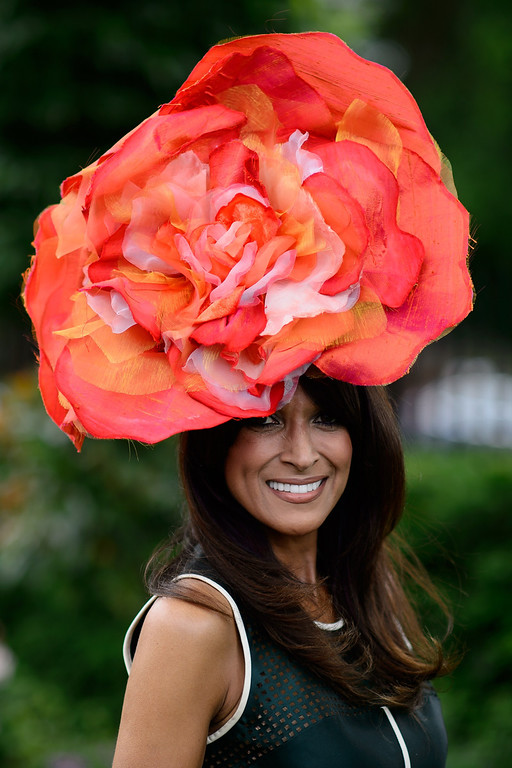 . A racegoer poses for photographers on the second day of the Royal Ascot horse racing meet, in Berkshire, west of London, on June 18, 2014. AFP PHOTO / LEON  NEAL/AFP/Getty Images