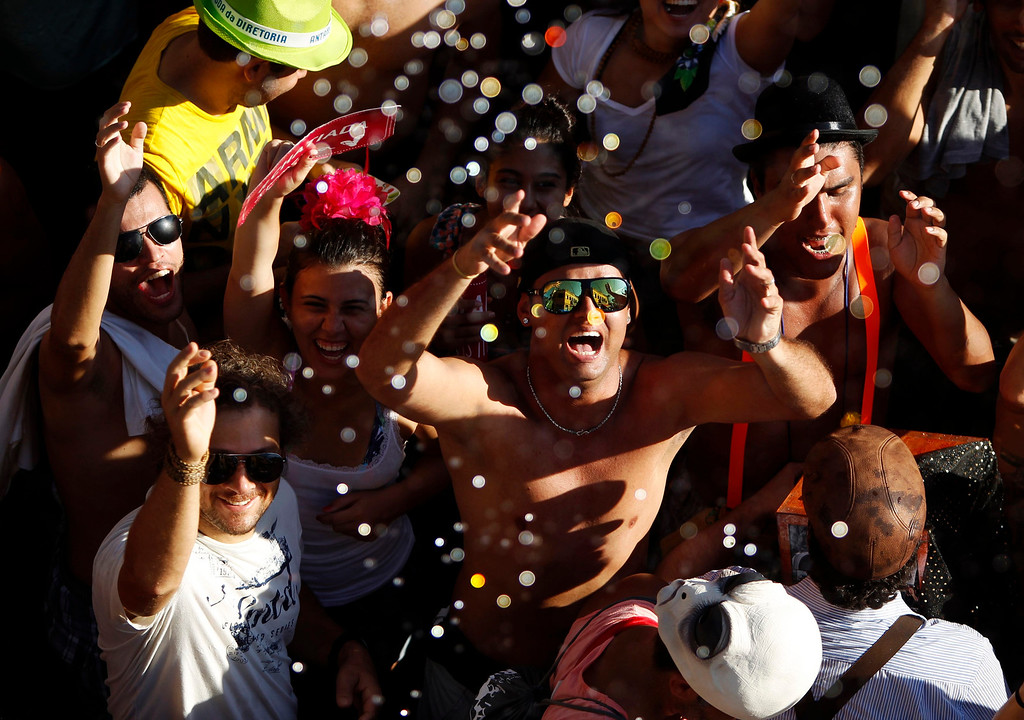 ". Water is sprinkled on revellers to help them cool off during an annual block party known as ""Ceu na Terra\"" (or Sky on Earth), one of the many carnival parties to take place in the neighborhoods of Rio de Janeiro February 2, 2013. REUTERS/Pilar Olivares"