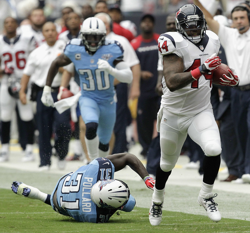 . Ben Tate #44 of the Houston Texans eludes the tackle of Bernard Pollard #31 of the Tennessee Titans as he rushes for long yardage in the first quarter at Reliant Stadium on September 15, 2013 in Houston, Texas.  (Photo by Bob Levey/Getty Images)