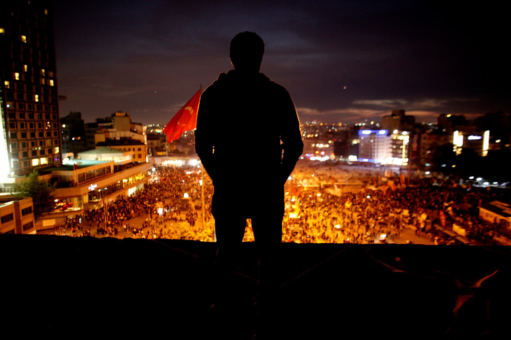 . A man standing on the roof of Ataturk Cultural center looks at protesters gathered at Taksim square in Istanbul, Tuesday, June 4, 2013.  (AP Photo/Kostas Tsironis)