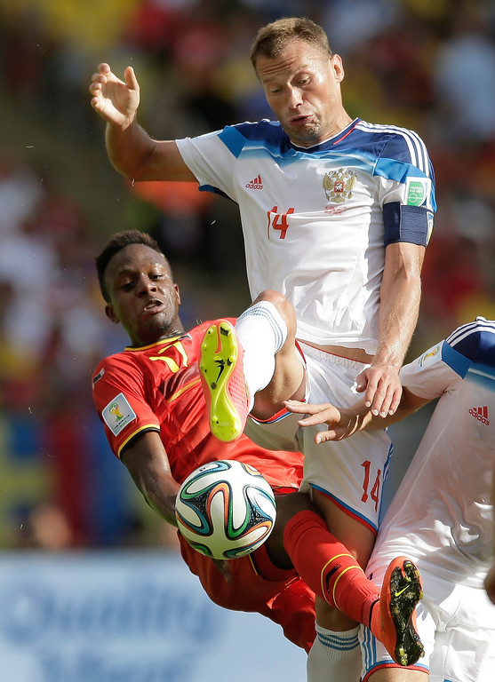 . Belgium\'s Divock Origi gets under Russia\'s Vasily Berezutsky (14) clear the ball during the group H World Cup soccer match between Belgium and Russia at the Maracana Stadium in Rio de Janeiro, Brazil, Sunday, June 22, 2014. (AP Photo/Bernat Armangue)