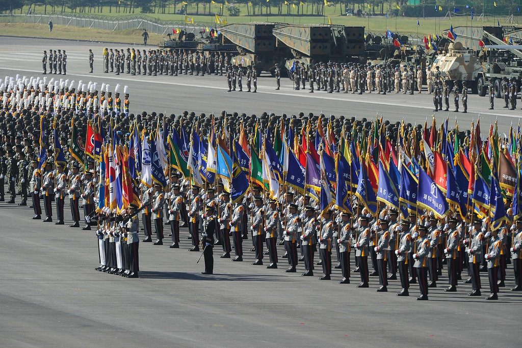 . South Korean army flags and troops line up at Seoul Air Base during the 65th anniversary of the Republic of Korea armed Forces day on September 27, 2013.  This year\'s event opened with the largest scale of military with eleven thousand of troops, some 190 armed vehicles and about 120 military aircrafts.     KIM DOO-HO/AFP/Getty Images
