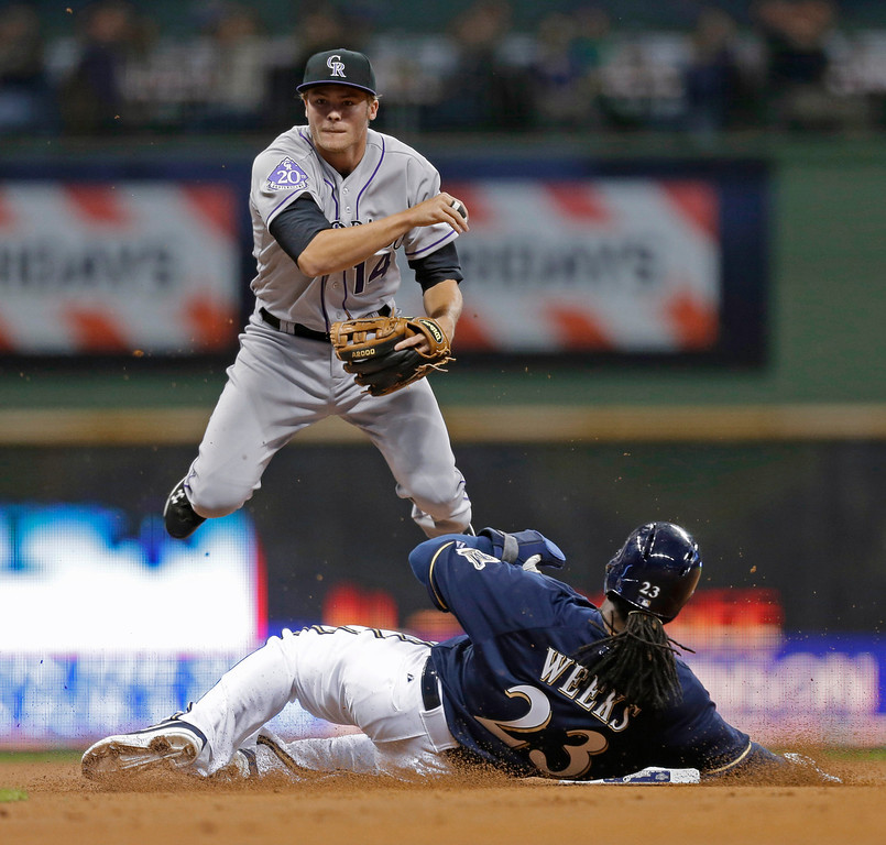 . Colorado Rockies\' Josh Rutledge (14) throws to first after forcing out Milwaukee Brewers\' Rickie Weeks at second base, completing a double play on Ryan Braun during the first inning of a baseball game Tuesday, April 2, 2013, in Milwaukee. (AP Photo/Jeffrey Phelps)