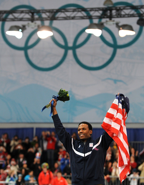 . US winner Shani Davis celebrates on the podium during the flowers ceremony after the men\'s 1000m speedskating final at the Richmond Oval on February 17, 2010 during the Vancouver Winter Olympics. AFP PHOTO  DIMITAR DILKOFF