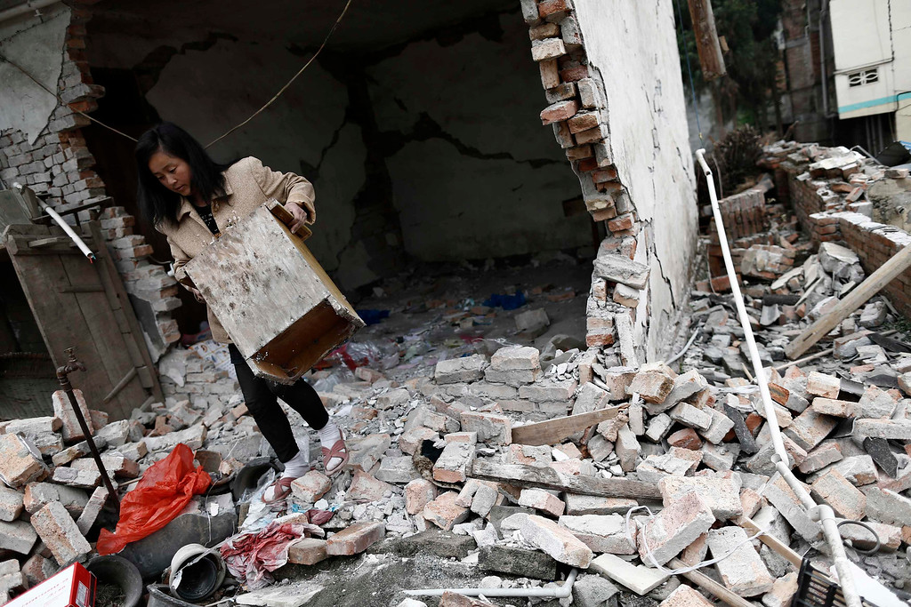 . A resident carries furniture out of her damaged house after Saturday\'s earthquake in Lingguan town of Baoxing county, Sichuan province  April 22, 2013. REUTERS/Aly Song