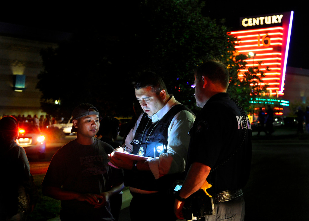 . An Aurora Police Department detective takes a witness statement following a mass shooting on July 20, 2012. Aurora Police responded to the Century 16 movie theatre early Friday morning on reports of a mass shooting. Karl Gehring, The Denver Post