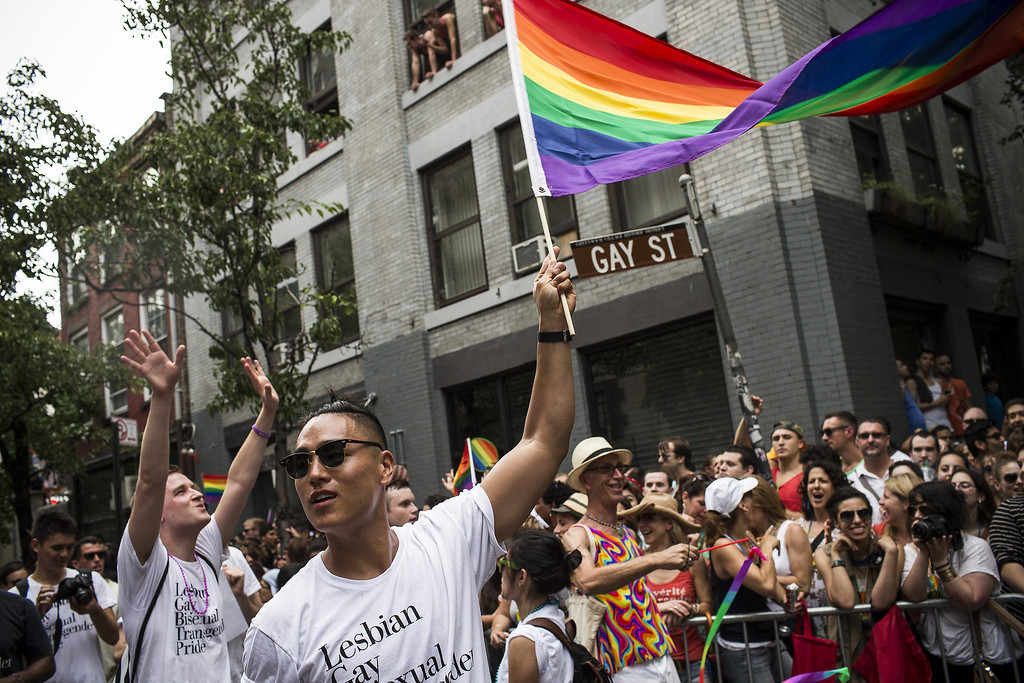 . Revelers march in the New York Gay Pride Parade on June 30, 2013 in New York City.  This year\'s parade was a particularly festive occasion, due to the recent Supreme Court Ruling that it was unconstitutional to ban gay marriage.  (Photo by Andrew Burton/Getty Images)
