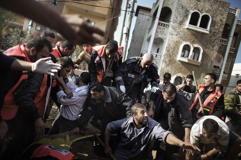. A Palestinian man calls for help as he and others try to save a man  trapped under his car just after an Israeli air raid on the area of Twaam in the northern Gaza town of Beit Lahia on November 15, 2012. Israeli air strikes have killed more than ten Gazans, including top Hamas commander Ahmed Jaabari, as three Israelis die when a rocket strikes a house, in the latest flareup of tit-for-tat fighting. (MARCO LONGARI/AFP/Getty Images)