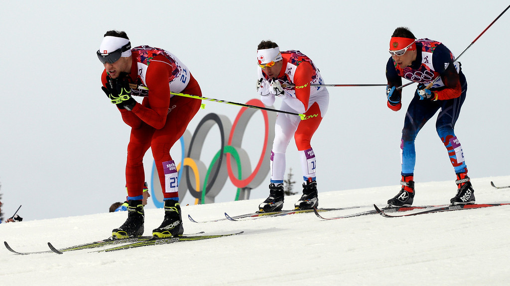 . Switzerland\'s Dario Cologna leads other competitors on his way to win the men\'s cross-country 30k skiathlon, at the 2014 Winter Olympics, Sunday, Feb. 9, 2014, in Krasnaya Polyana, Russia. (AP Photo/Lee Jin-man)