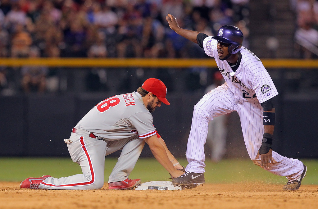 . DENVER, CO - JUNE 14:  Dexter Fowler #24 of the Colorado Rockies steals second base while pinch running as second baseman Kevin Frandsen #28 of the Philadelphia Phillies makes the late tag in the eighth inning at Coors Field on June 14, 2013 in Denver, Colorado.  (Photo by Doug Pensinger/Getty Images)