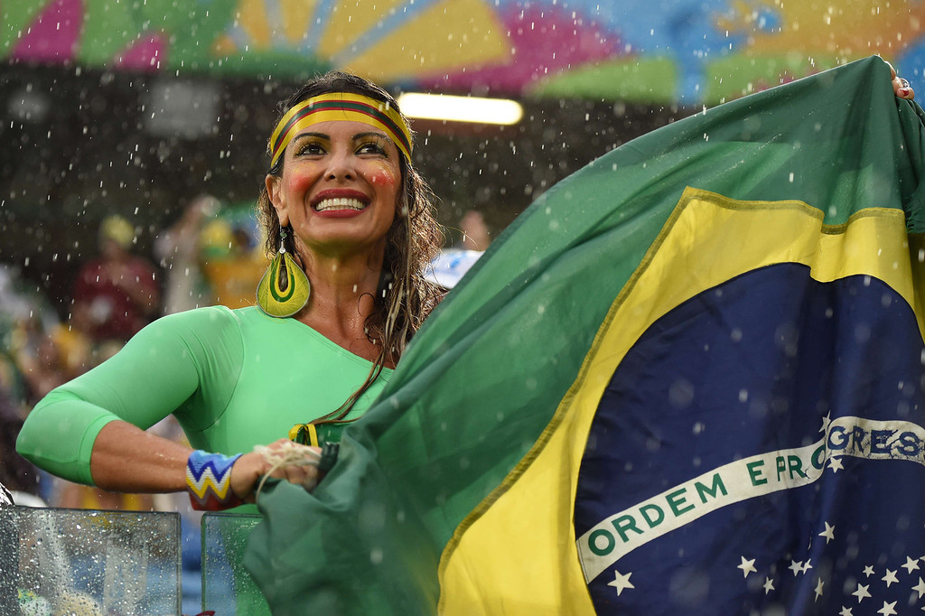 . A fan holds the Brazilian flag during a Group A football match between Mexico and Cameroon at the Dunas Arena in Natal during the 2014 FIFA World Cup on June 13, 2014. CHRISTOPHE SIMON/AFP/Getty Images