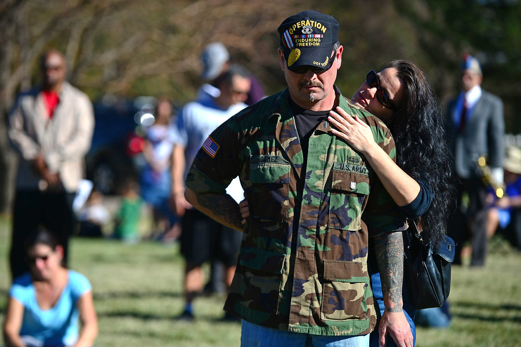 ". Joy Rose caresses the face of her boyfriend former army Sgt. Mike Gomez during the 36th annual Remembrance ceremony of Veteran\'s Day at Fort Logan Cemetery in Lakewood, CO  on November 11, 2013. The day was marked with a 21 gun rifle salute, ""Echo taps\"" played by buglers and the release of white birds of freedom.  The benediction was given by Jackie Newlander.  (Photo By Helen H. Richardson/ The Denver Post)"