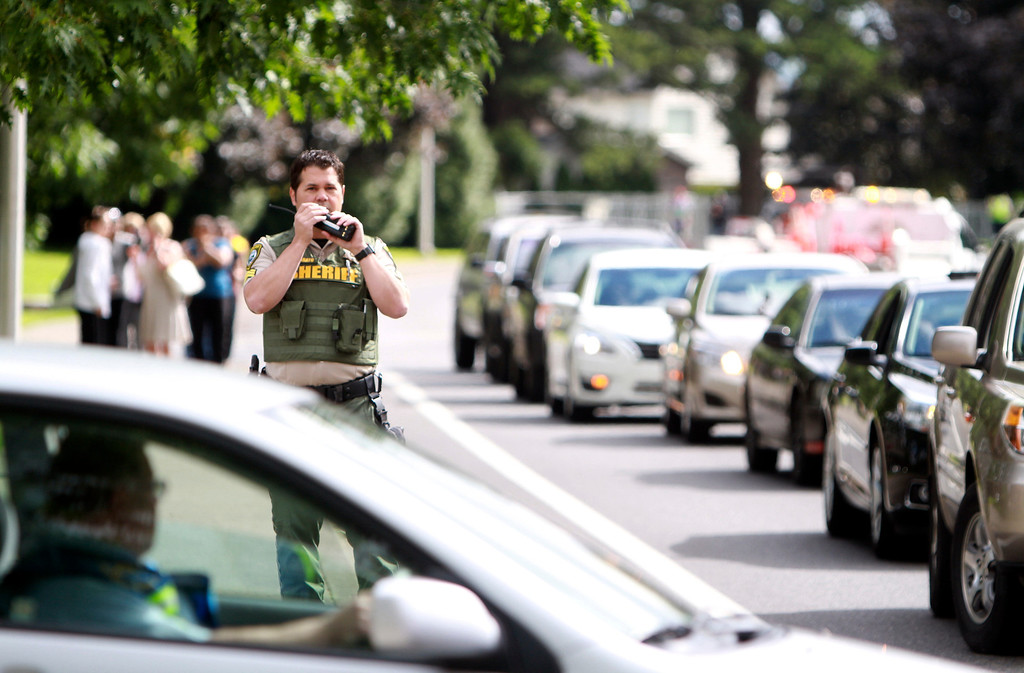 . A sheriff\'s officer speaks in this radio after a shooting at Reynolds High School Tuesday, June 10, 2014, in Troutdale, Ore.  (AP Photo/The Oregonian, Faith Cathcart)