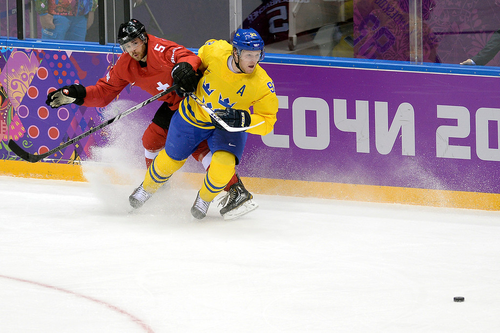 . Switzerland\'s Severin Blindenbacher defends Sweden\'s Gabriel Landeskog during the action at Bolshoy Arena. Sochi 2014 Winter Olympics on Friday, February 14, 2014. (Photo by AAron Ontiveroz/The Denver Post)
