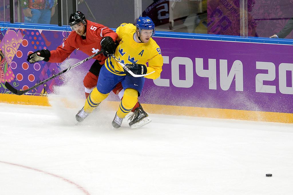 . Switzerland\'s Severin Blindenbacher defends Sweden\'s Gabriel Landeskog during the action at Bolshoy Arena. Sochi 2014 Winter Olympics on Friday, February 14, 2014. (Photo by AAron Ontiveroz/The Denver Post)