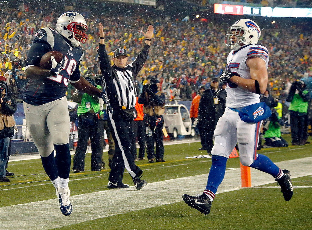 . New England Patriots running back LeGarrette Blount (29) scores a touchdown past Buffalo Bills safety Jim Leonhard (35) in the second quarter of an NFL football game, Sunday, Dec. 29, 2013, in Foxborough, Mass. (AP Photo/Elise Amendola)
