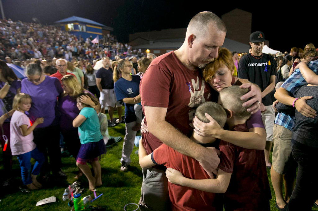 . Fred Dangler and Nicole Gambill of Prescott, Ariz. embrace their children Evan, 9, right and Aidan, 8, during a candlelight vigil for the 19 firefighters killed battling the Yarnell Hill Fire, on the football field at Prescott High School in Prescott on Tuesday, July 2, 2013. (AP Photo/The Arizona Republic, David Wallace)