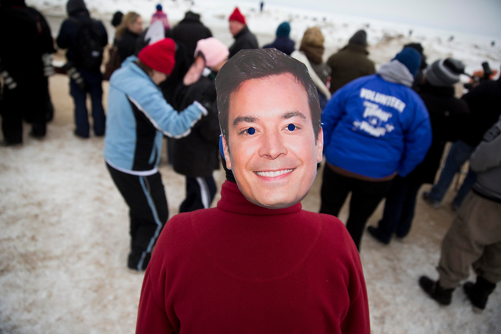 """. Kay Golden, of Chicago, wears a Jimmy Fallon mask on the back of her head while waiting for the start of the Chicago Polar Plunge on Sunday, March 2, 2014, in Chicago. Chicago Mayor Rahm Emanuel and \""""The Tonight Show\"""" host Jimmy Fallon entered the water during the event. (AP Photo/Andrew A. Nelles)"""