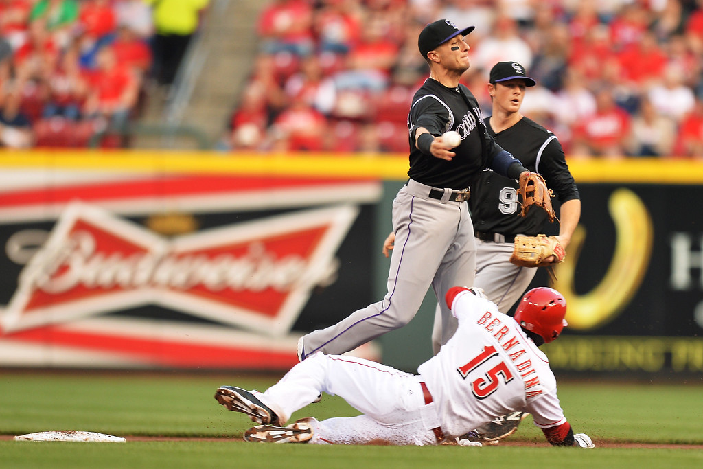 . CINCINNATI, OH - MAY 10:  Troy Tulowitzki #2 of the Colorado Rockies throws to first base to complete a double play to end the second inning after forcing out Roger Bernadina #15 of the Cincinnati Reds at Great American Ball Park on May 10, 2014 in Cincinnati, Ohio.  (Photo by Jamie Sabau/Getty Images)