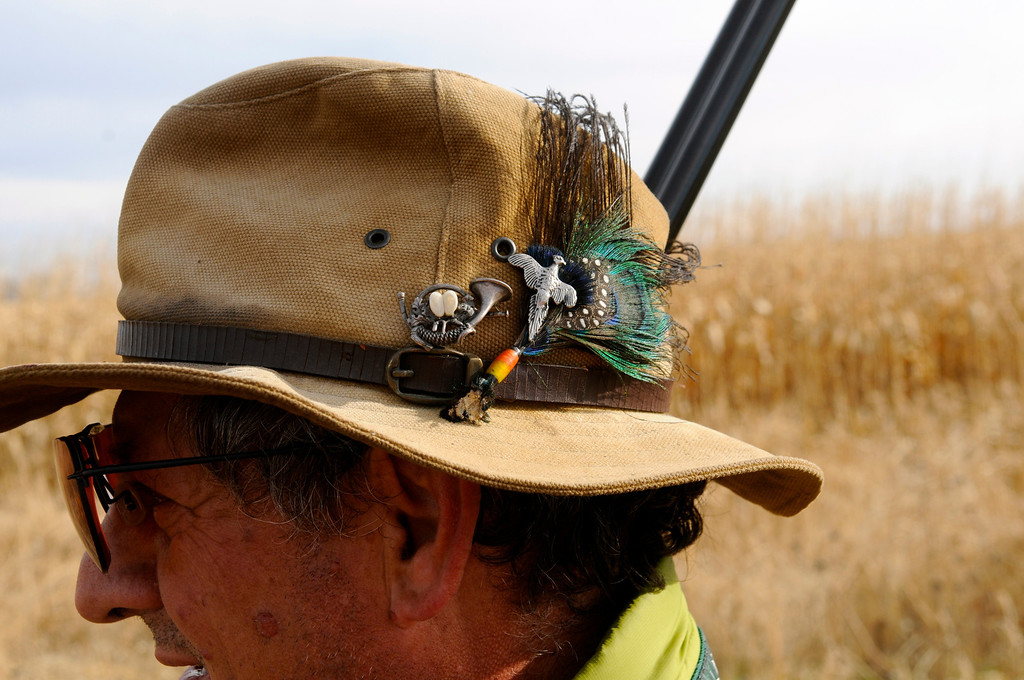 . Javier Gonzalez-Bringas, a Carbondale resident originally from Spain, shows off his well-traveled hunting hat that includes charms and exotic feathers from Africa. Scott Willoughby, The Denver Post