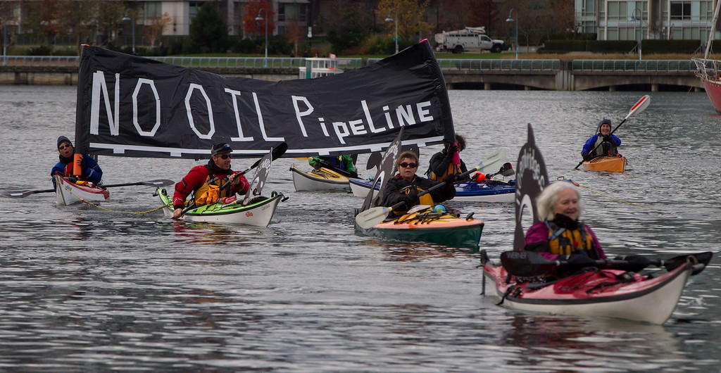 """. Kayakers display a \""""No Oil Pipeline\"""" banner during a protest against the Enbridge Northern Gateway pipeline in Vancouver, on Saturday Nov. 16, 2013.   (AP Photo/The Canadian Press, Darryl Dyck)"""