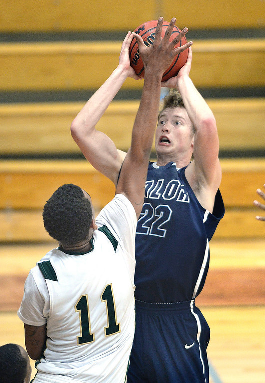. Eagles\' senior Chase Foster (22) put up a jump shot over Trojans\' forward Thaleel Khabir (11) in the second half. The Valor Christian High School boy\'s basketball team defeated Aurora Central 60-52 Wednesday night, January 8, 2014. Photo By Karl Gehring/The Denver Post
