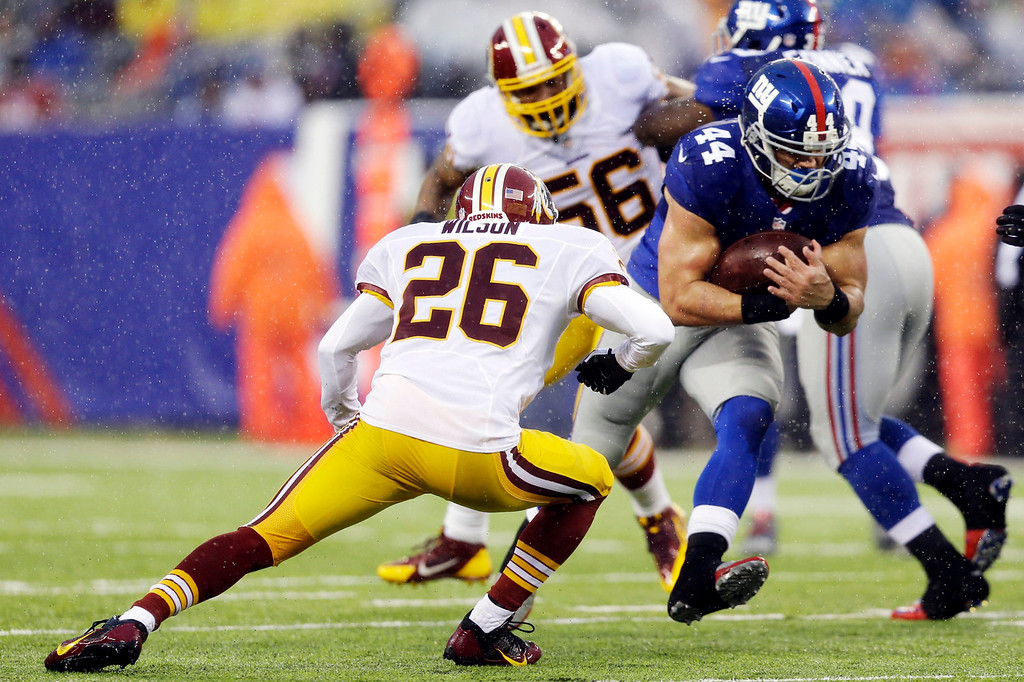 . New York Giants running back Peyton Hillis (44) rushes as Washington Redskins\' Josh Wilson (26) attempts to tackle him during the first half of an NFL football game on Sunday, Dec. 29, 2013, in East Rutherford, N.J.  (AP Photo/Julio Cortez)